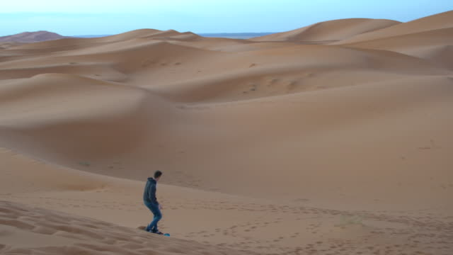 Tourist sand-boarding at Erg Chebbi dunes early in the morning, Saharan Morocco