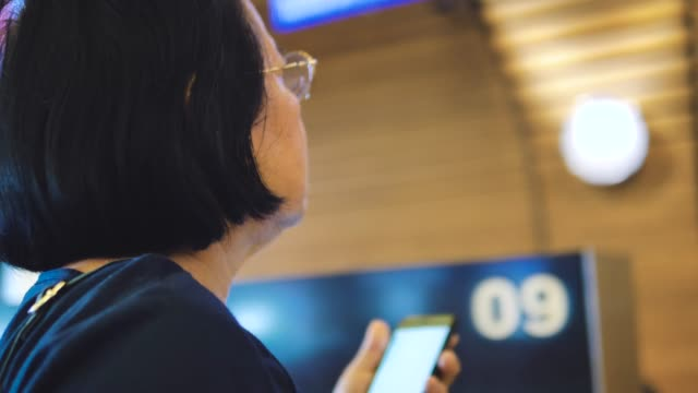 Touristischen senior Frau sitzen auf Sitz und mit Smartphone auf Zug.