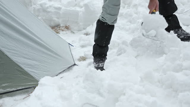 tourist setting up tent while camping in winter mountain. alone in nature while covid-19 pandemic. mental health and life balance. - tent stock videos & royalty-free footage