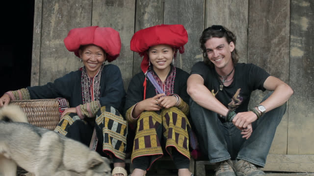 A tourist sits with three Red Zao tribeswomen as a dog walks by.