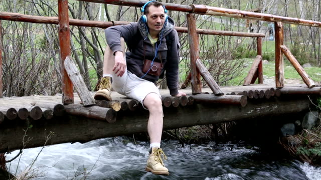 tourist sitting on a wooden bridge and enjoying the music - one mid adult man only stock videos & royalty-free footage