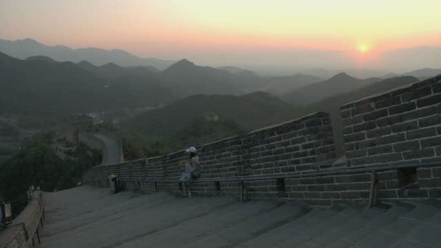 ws tourist sitting on bench at badaling pass of great wall of china / beijing, china - badaling great wall stock videos & royalty-free footage