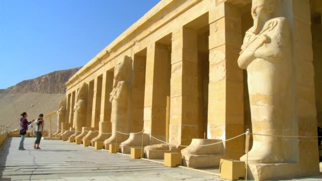 vídeos de stock, filmes e b-roll de ws tu tourist standing at hatshepsut's temple / luxor, egypt - templo de hatshepsut