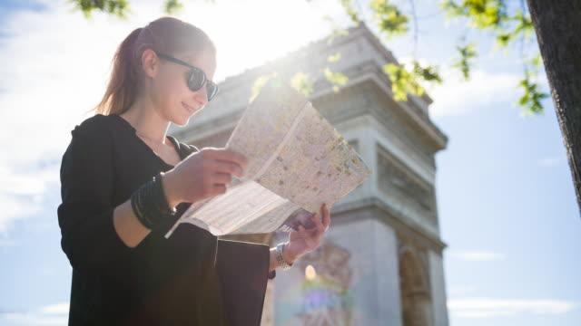 vídeos de stock e filmes b-roll de tourist standing in front of arch of triumph in paris, reading city map - ensolarado