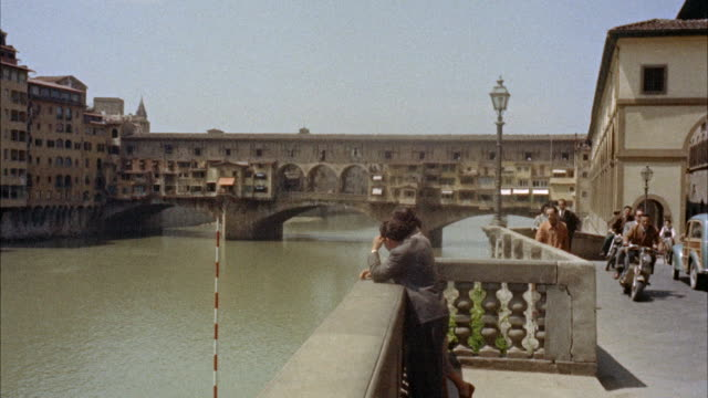 ms  tourist standing on  ponte vecchio bridge over arno river / florence, italy  - florence italy stock videos and b-roll footage