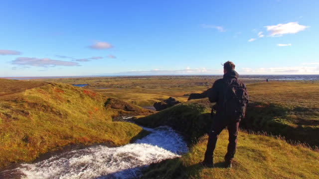 aerial tourist stands by the river in iceland - wide angle stock videos & royalty-free footage
