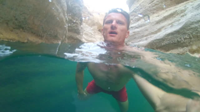 pov tourist swimming in wadi shab - natural landmark stock videos & royalty-free footage