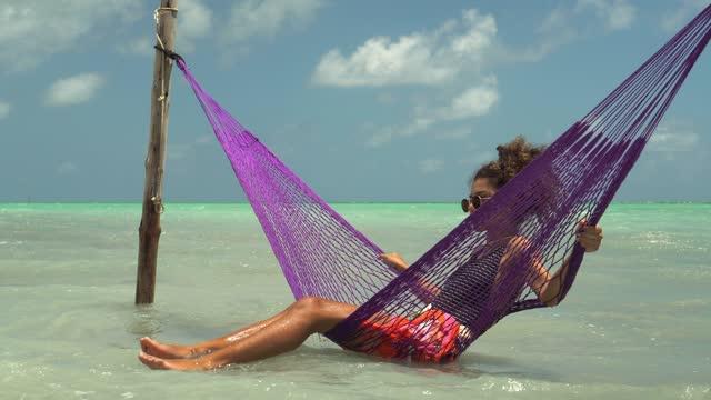 tourist swinging on the hammock at maragogi beach - swimming costume stock videos & royalty-free footage