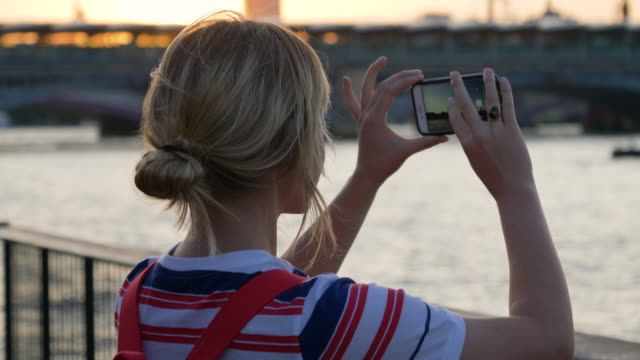 tourist takes photo of sunset over urban skyline and looks at the results. - ein tag im leben stock-videos und b-roll-filmmaterial
