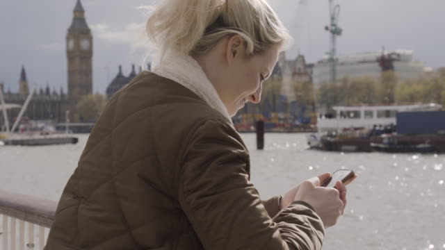 Tourist takes photo of view of river Thames, she sends the images and looks up into the sunshine.