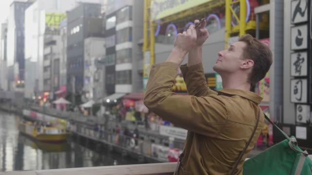 vídeos de stock e filmes b-roll de tourist takes pictures on the bridge of tonbori river in dotonbori - photo messaging