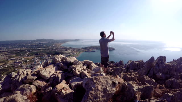 Tourist takes selfie on top of mountain