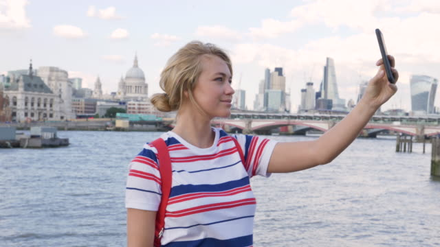 tourist takes selfies on phone, london city skyline in background. - city of london stock videos & royalty-free footage