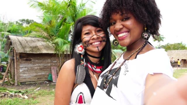 vídeos de stock, filmes e b-roll de turísticos, levando um selfie com a mulher indígena guarani em uma aldeia - cultura indígena