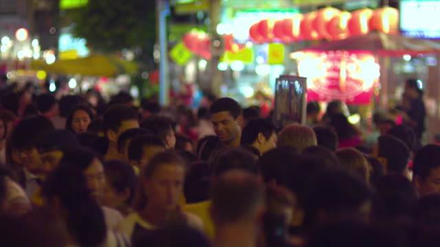 ms selective focus tourist taking photos at crowded street festival at night, bangkok, ayuthaya, thailand - see other clips from this shoot 1448 stock videos and b-roll footage