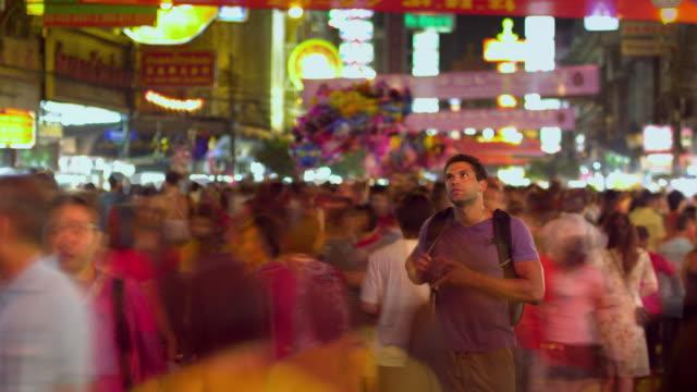 T/L MS Tourist taking photos at crowded street festival at night, Bangkok, Ayuthaya, Thailand