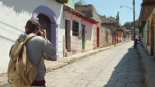 vídeos y material grabado en eventos de stock de tourist taking pictures of a colonial-style street in san cristobal de las casas, chiapas, mexico - pared de cemento