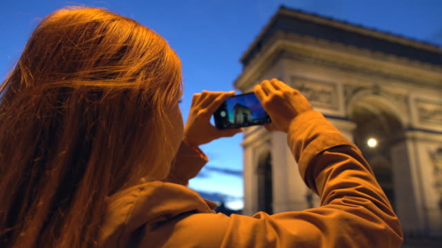 tourist taking pictures of arc de triomphe with phone at night - french revolution stock videos and b-roll footage