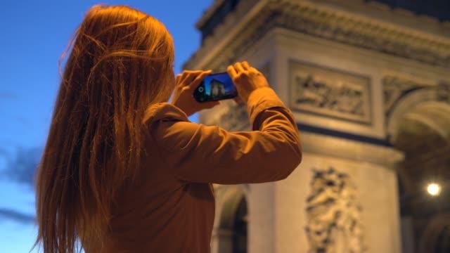 vidéos et rushes de touriste prenant des photos de l'arc de triomphe avec téléphone dans la nuit - arc élément architectural