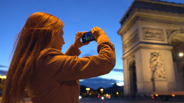 Tourist taking pictures of Arc de Triomphe with smartphone at night