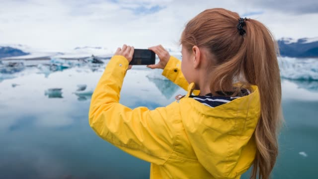 tourist taking pictures of icebergs with smartphone - photographing stock videos & royalty-free footage