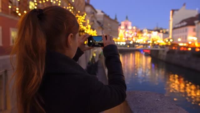 vídeos y material grabado en eventos de stock de turistas tomando fotos de ljubljana en navidad - con mucha luz