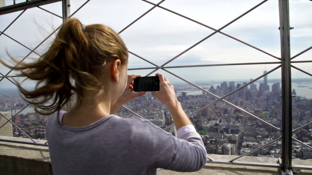 turista scattare foto di manhattan, new york city - empire state building video stock e b–roll