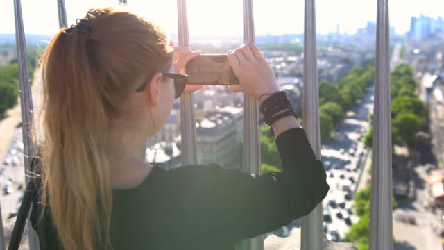 tourist taking pictures of paris from top of arch of triumph - arco architettura video stock e b–roll