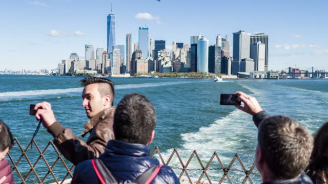 Tourist taking pictures to Manhattan leaving to Staten Island