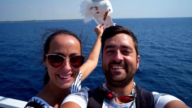 Tourist taking selfie while feeding seagulls in flight
