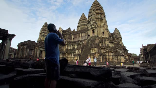 tourist talking on the phone at angkor wat temple, cambodia - famous place stock videos & royalty-free footage