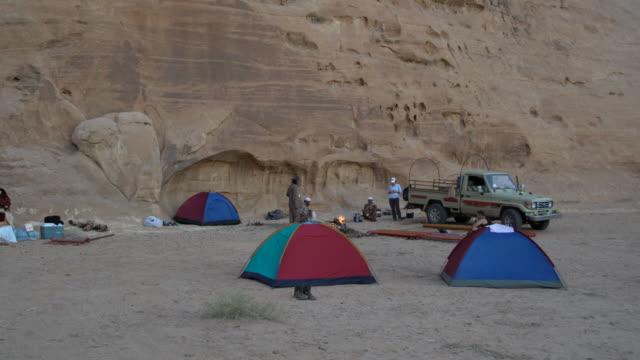 tourist tents in front of a huge sandstone rock in wadi rum desert, jordan - sandstone stock videos & royalty-free footage
