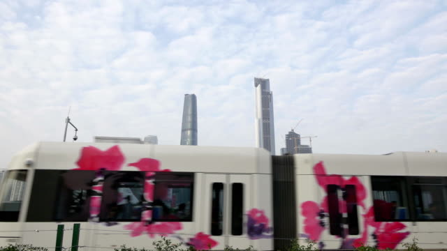 tourist train travel through modern city guangzhou with skyline as background. - tourist train stock videos and b-roll footage