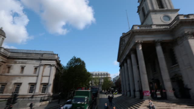tourist pov travels around trafalgar square towards the national gallery and st martin-in-the-fields church on sunny day in london. - トラファルガー広場点の映像素材/bロール