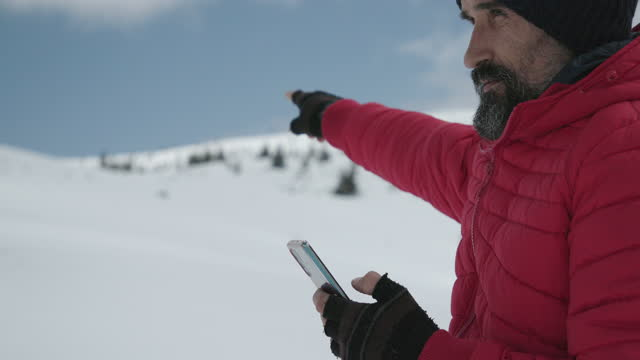 tourist using gps on his phone while hiking in the winter mountain on a sunny day. alone in nature while covid-19 pandemic. mental health and life balance. - one mature man only stock videos & royalty-free footage