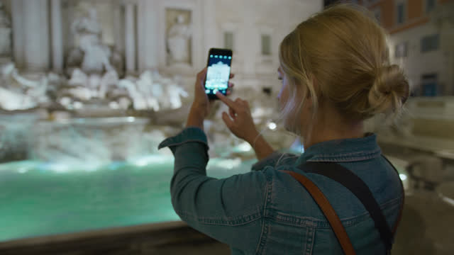 slo mo tourist using her smartphone to take pictures of the trevi fountain at night - italian culture stock videos & royalty-free footage