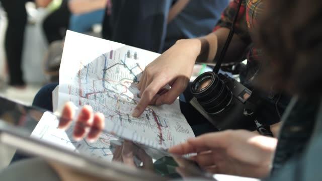 vídeos y material grabado en eventos de stock de turismo en mapa guía para el mapa de metro con tableta digital - orientación