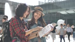 Tourist using Map in Guide Book with friend in the city