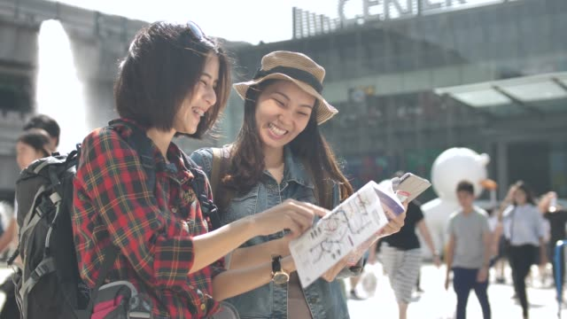 tourist using map in guide book with friend in the city - asian stock videos & royalty-free footage
