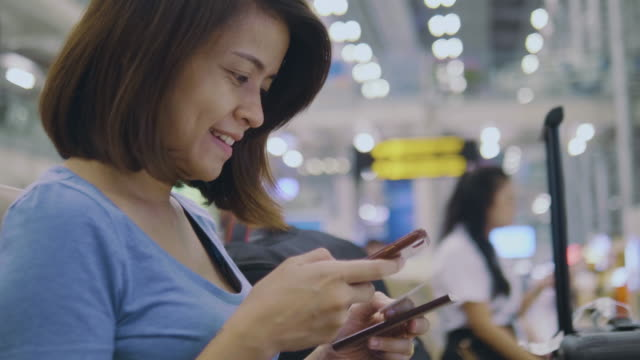 vídeos de stock, filmes e b-roll de turista usando telefone para check-in on-line no aeroporto - vale