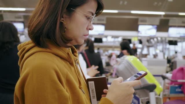 観光オンライン空港チェックインのため電話を使用 - 飛行機の搭乗券点の映像素材/bロール