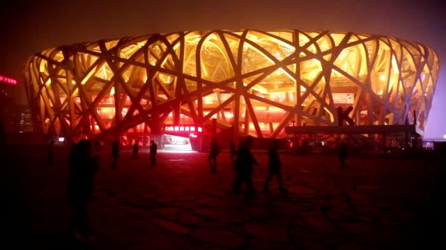 beijing, сhina - october 14, 2016: tourist visit beijing bird nest stadium at night with lights on under haze pollution. - bird's nest stock videos and b-roll footage