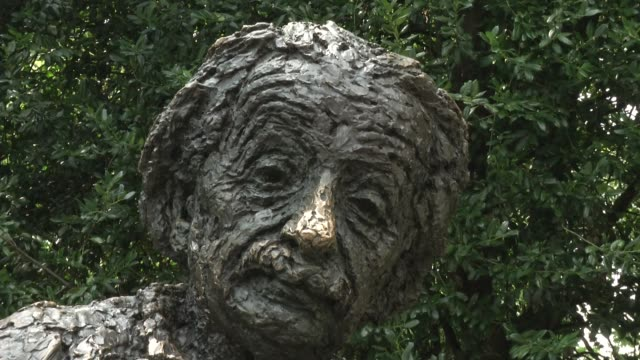 stockvideo's en b-roll-footage met tourist visit the albert einstein memorial in washington dc it is a monumental bronze statue depicting albert einstein seated with manuscript papers... - albert einstein