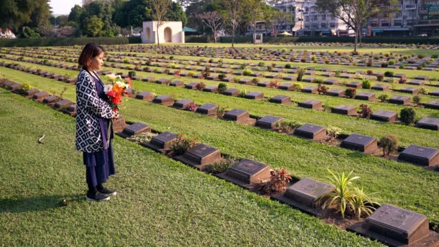 tourist besuchen den friedhof des zweiten weltkriegs mit blumen in kanchanaburi, thailand. - world war ii stock-videos und b-roll-filmmaterial