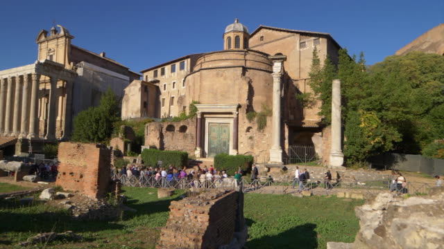 tourist walk past the temple of romulus at the roman forum in rome, italy - menschliche siedlung stock-videos und b-roll-filmmaterial