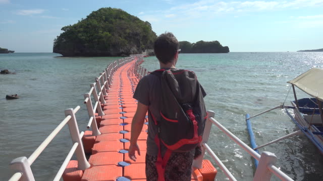tourist walking along floating bridge at philippines hundred islands - floating moored platform stock videos & royalty-free footage