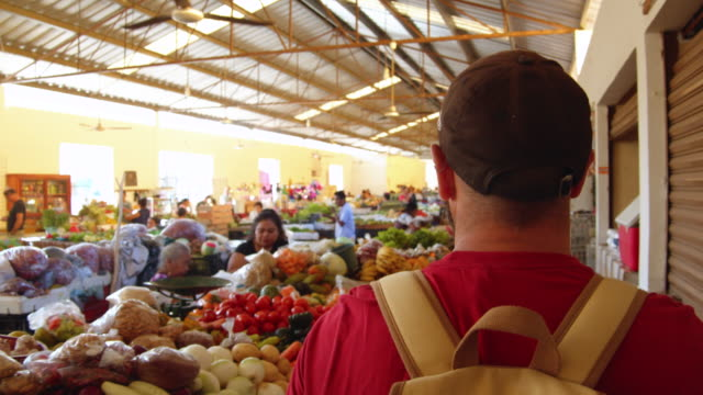 tourist walking along mexican vegetable market stalls. valladolid, yucatan - rucksack stock videos & royalty-free footage