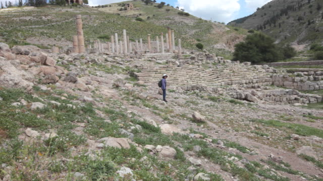 a tourist walking among the remains from the ancient hellenistic and roman cities in pella, jordan - archäologie stock-videos und b-roll-filmmaterial