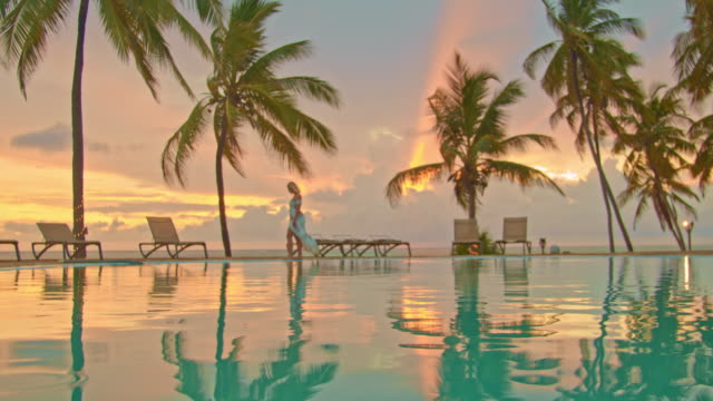 slo mo tourist walking by the edge of the pool on the beach at sunset - infinity pool stock videos & royalty-free footage
