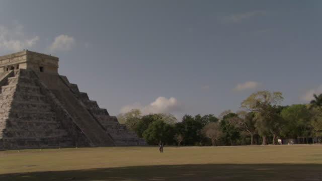 vídeos de stock e filmes b-roll de ws pan tourist walking near kukulkan pyramid at ancient mayan site chichen itza / yucatan, mexico  - por volta do século 7 dc